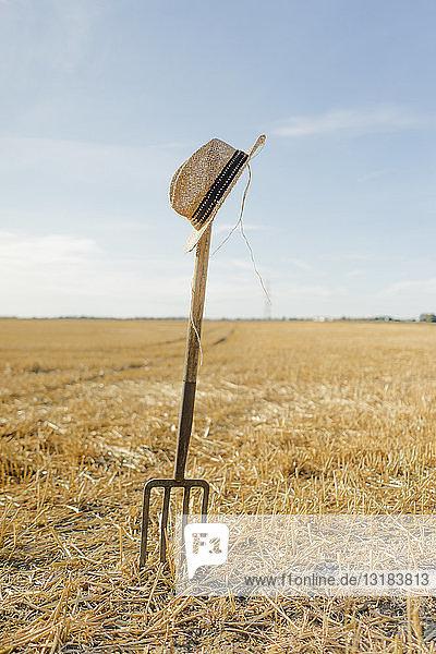 Strohhut auf Mistgabel im Feld in ländlicher Landschaft