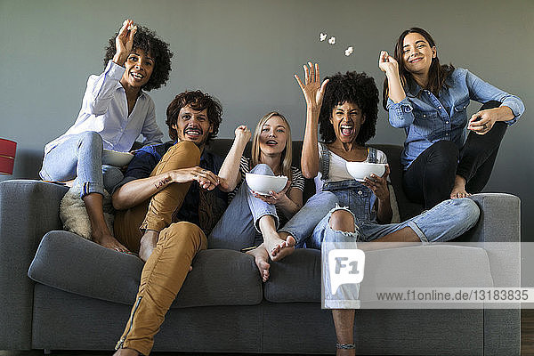Überschwängliche Freunde sitzen auf der Couch und sehen fern