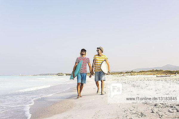 Freunde  die am Strand spazieren gehen und Surfbretter tragen