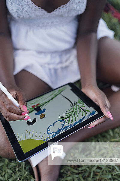 Close-up of young woman in a park drawing on graphics tablet