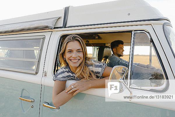 Porträt einer glücklichen Frau  die sich aus dem Fenster eines Wohnmobils lehnt  während ein Mann fährt