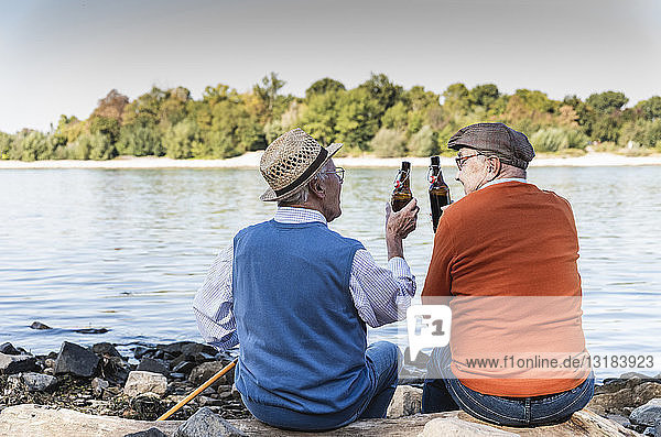 Old friends sitting by the riverside  drinking beer