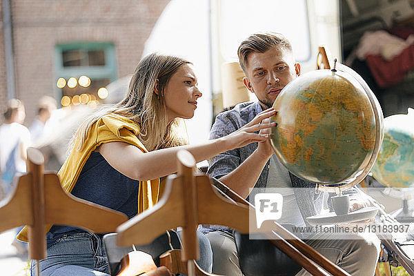 Belgien  Tongeren  junges Paar untersucht den Globus auf einem Antiquitäten-Flohmarkt Belgien, Tongeren, junges Paar untersucht den Globus auf einem Antiquitäten-Flohmarkt