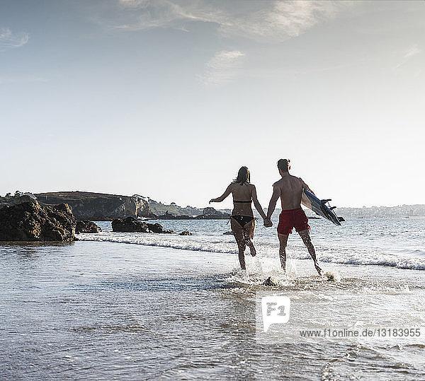 Frankreich,  Bretagne,  junges Paar mit einem Surfbrett,  das Hand in Hand im Meer läuft