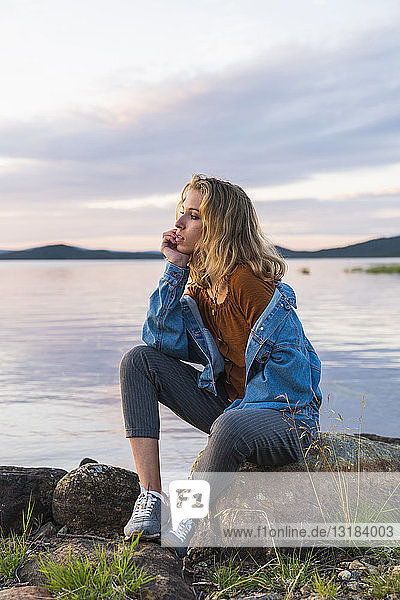 Finland  Lapland  young woman sitting on a rock at the lakeside