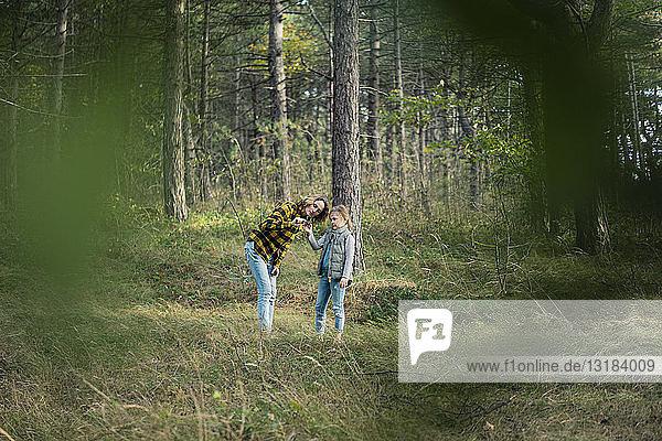 Mutter und Tochter erkunden die Natur im Wald