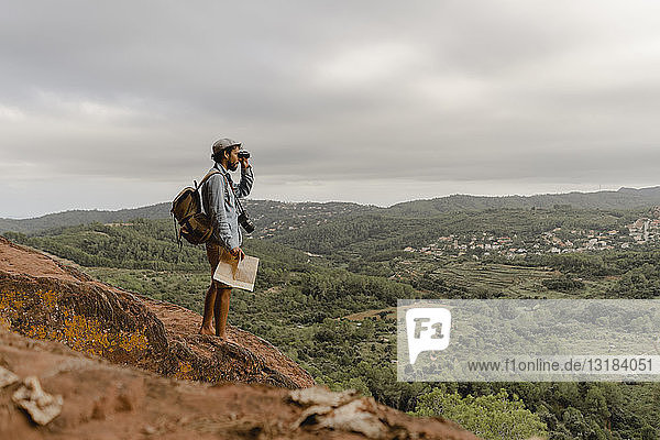 Young man with backpack  standing on a mountain  looking at view  using field glasses
