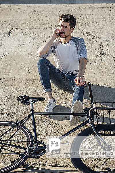Junger Mann mit Pendler-Fixie-Fahrrad sitzt auf Betonwand und telefoniert