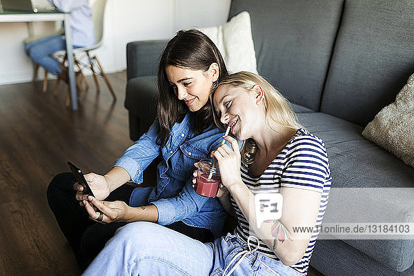Two smiling young women sitting on floor with soft drink sharing cell phone