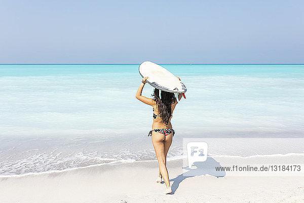 Junge Frau trägt Surfbrett ins Meer