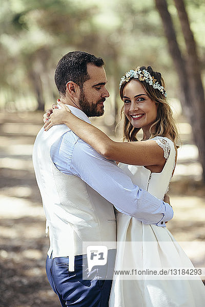 Portrait of happy bride dancing with her groom in pine forest