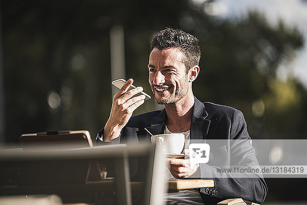 Businessman sitting in cafe  drinking coffee  using smartphone