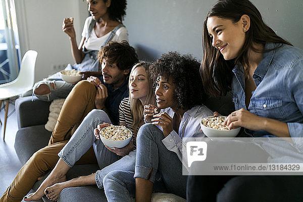 Freunde sitzen auf der Couch und sehen fern