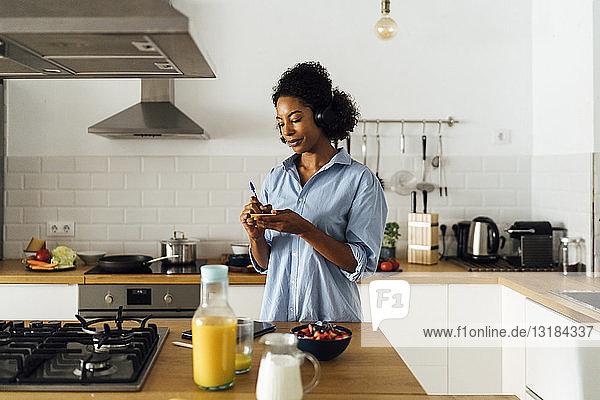 Frau morgens in ihrer Küche und schreibt Notizen