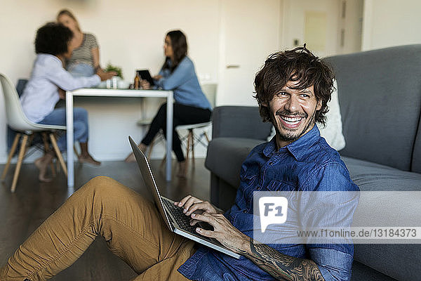 Laughing man sitting on floor using laptop with friends in background