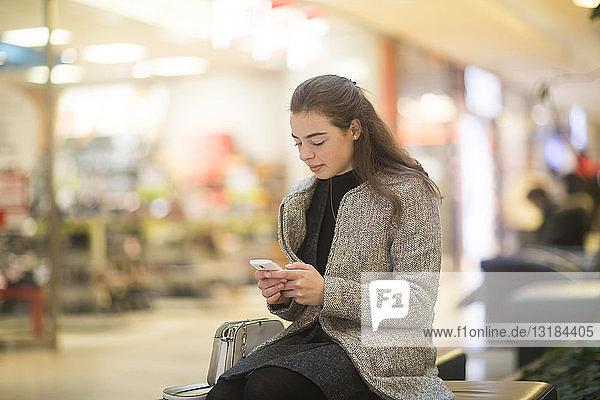 Junge Frau benutzt Smartphone im Geschäft