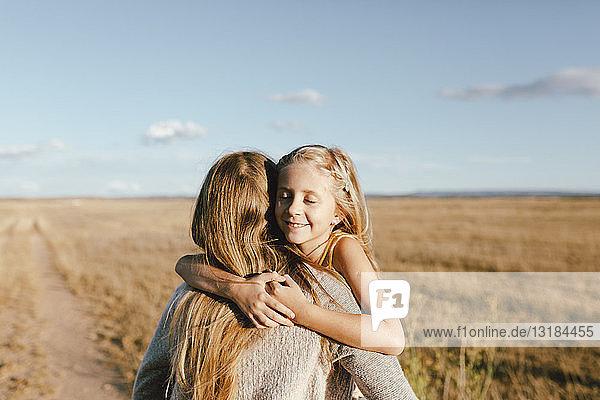 Lächelnde Tochter umarmt Mutter auf einem Feld