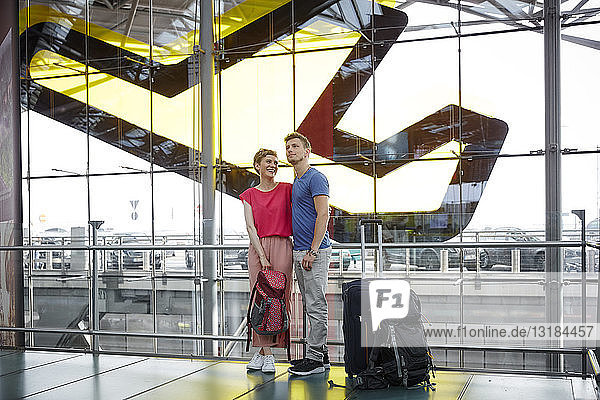 Smiling couple standing at the airport