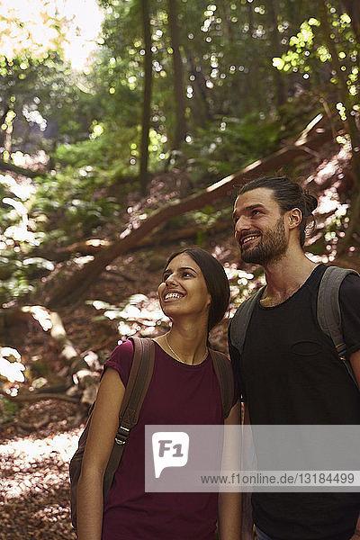 Spanien  Kanarische Inseln  La Palma  lächelndes Paar steht in einem Wald und schaut sich um