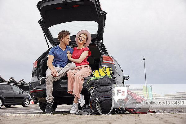 Glückliches junges Paar sitzt im Kofferraum eines Autos auf dem Flughafen