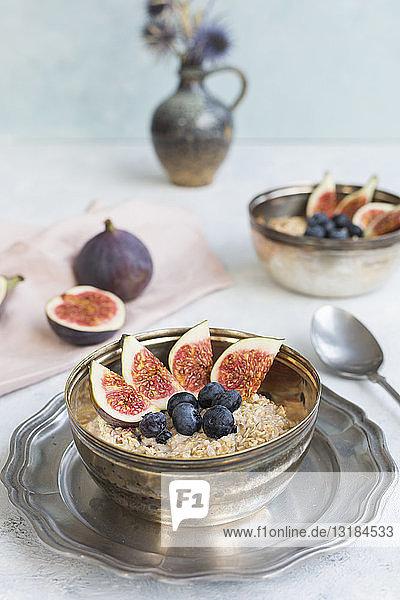 Schüssel Brei mit in Scheiben geschnittenen Feigen  Blaubeeren und getrockneten Beeren