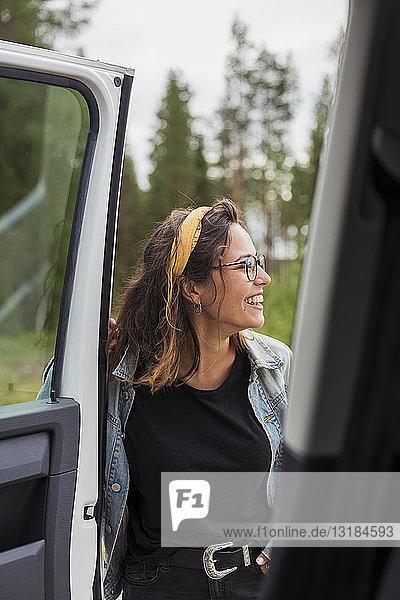 Finnland  Lappland  glückliche junge Frau an einem Auto in ländlicher Landschaft