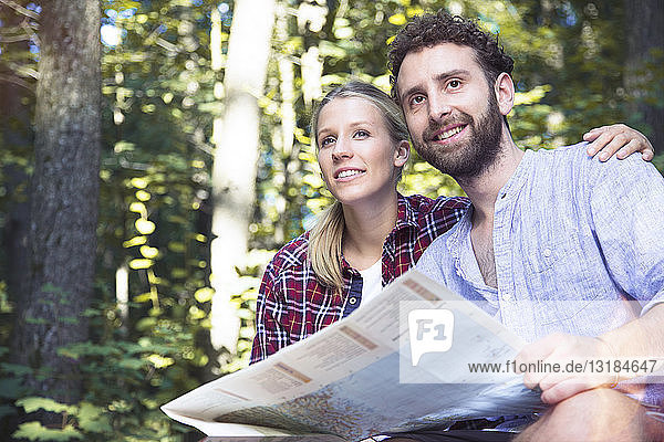 Smiling young couple with map in a forest