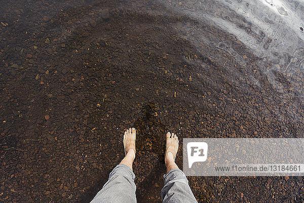 Füße eines Mannes im Wasser eines Sees