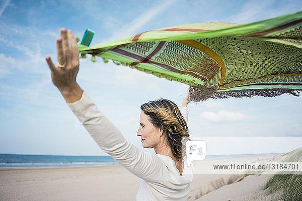 Reife Frau hält flatterndes Tuch im Wind  Relaxiang in den Dünen