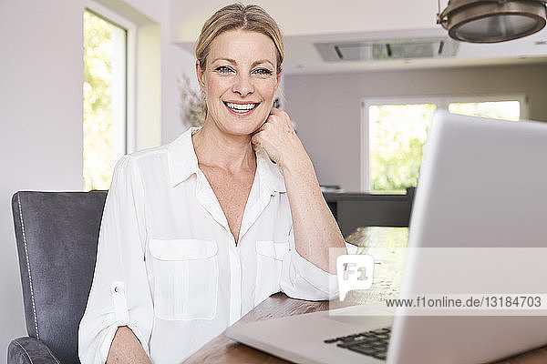 Porträt einer lächelnden Geschäftsfrau mit Laptop zu Hause