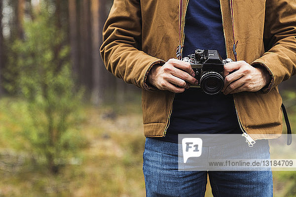 Finland,  Lapland,  close-up of man holding camera in rural landscape