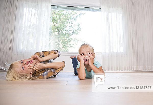 Bruder und Schwester liegen zu Hause auf dem Boden und ziehen eine Grimasse