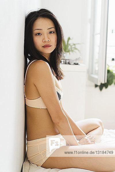 Porträt einer attraktiven jungen Frau in Dessous auf dem Bett sitzend