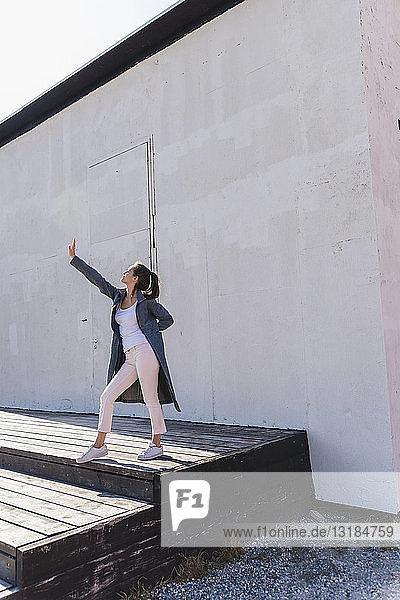 Junge Frau gestikuliert vor einer Wand