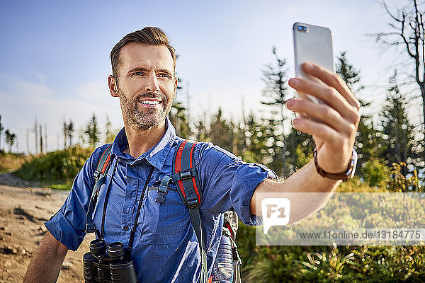 Man taking a selfie with his cell phone during hiking trip in the mountains