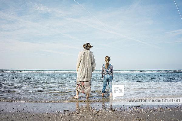 Mutter und Tochter am Strand stehend  auf das Meer blickend  Rückansicht