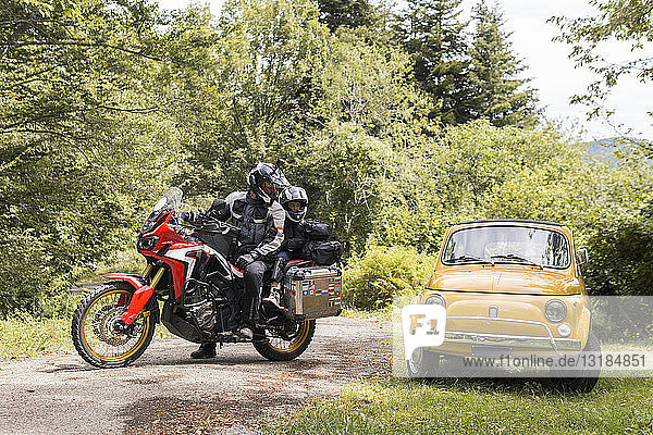 Father and son on a motorbike trip on a country road stopping beside compact car