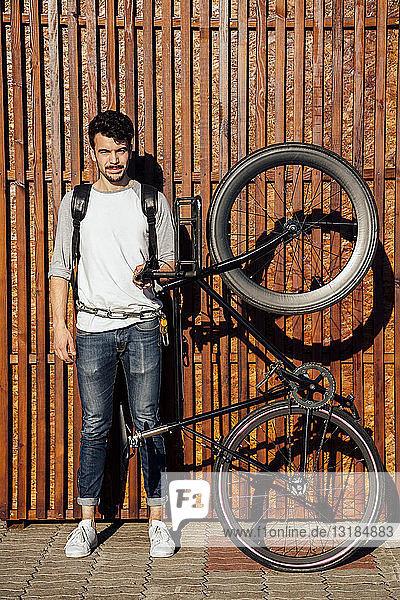 Porträt eines jungen Mannes mit Rucksack  der ein Pendler-Fixie-Fahrrad hält
