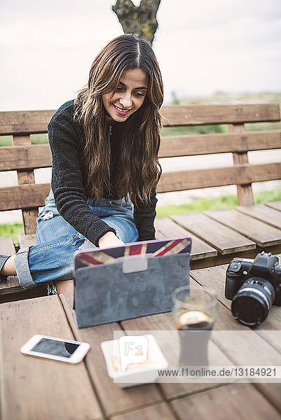 Portrait of smiling young woman sitting on bench outdoors using tablet