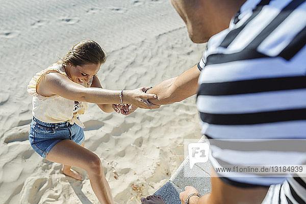 Mann hilft Frau beim Aufstieg vom Strand