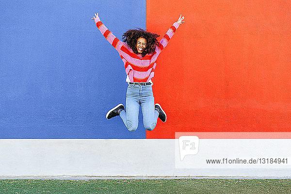 Glückliche junge Frau springt in die Luft