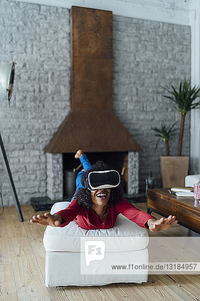 Woman lying on seating furniture  wearing VR goggles  pretending to fly