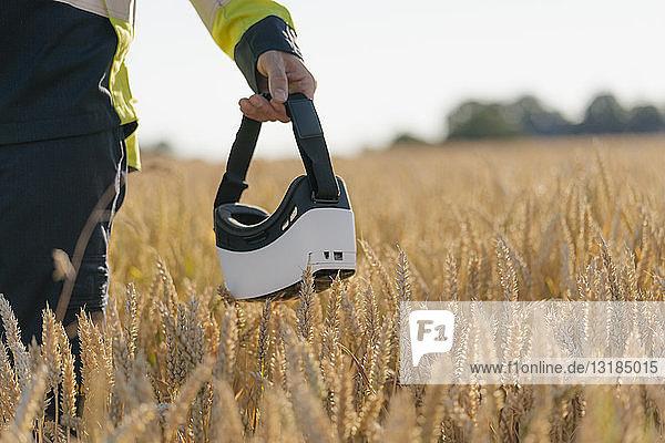 Nahaufnahme eines Mannes in Arbeitsschutzkleidung und VR-Brille in einem Feld
