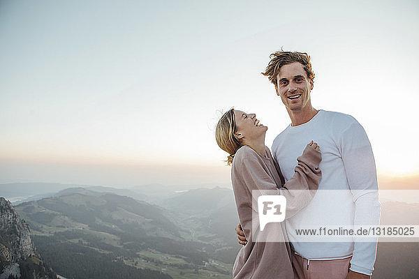 Schweiz  Grosse Mythen  Porträt eines glücklichen jungen Paares  das bei Sonnenaufgang in einer Berglandschaft steht