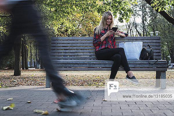Junge Frau mit Einkaufstasche sitzt im Herbst mit Minitablette auf Bank