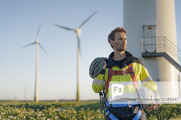 Techniker  der mit Kletterausrüstung an einem Windpark steht