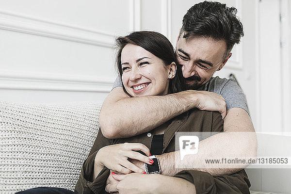 Glückliches Paar umarmt sich zu Hause