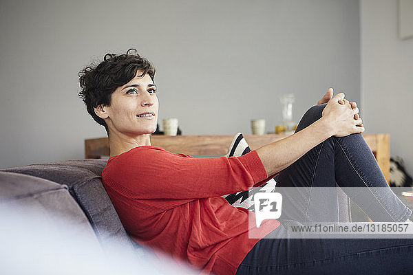 Portrait of smiling woman on couch at home thinking