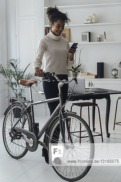 Mid adult woman leaving her home office  pushing bicycle  using smartphone
