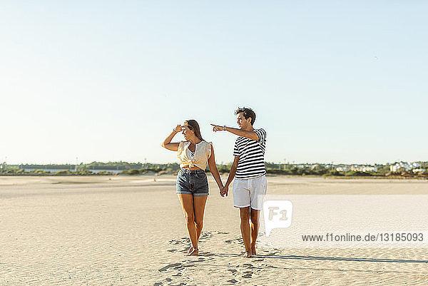 Junges Paar geht Hand in Hand am Strand